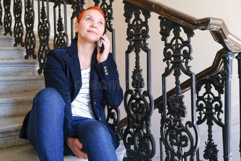 Meisje die SMS in smartphone lezen De emotie van blije verrassing Het korte kapsel van vrouwen Modieus modieus profiel met stock foto's