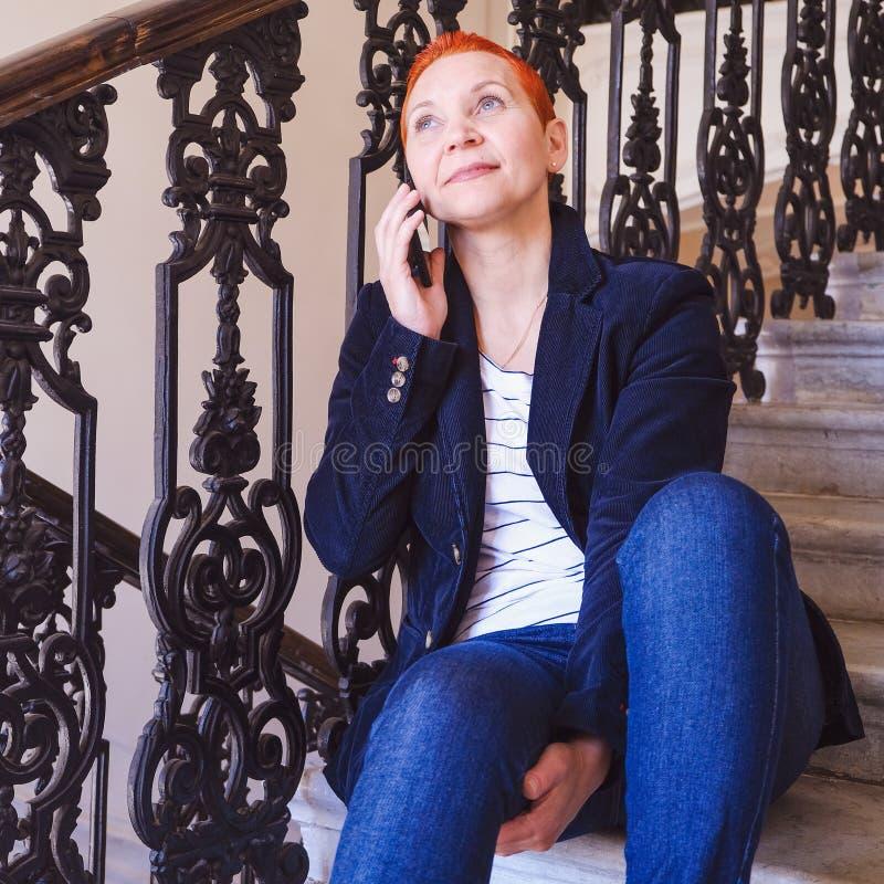 Meisje die SMS in smartphone lezen De emotie van blije verrassing Het korte kapsel van vrouwen Modieus modieus profiel met royalty-vrije stock afbeeldingen