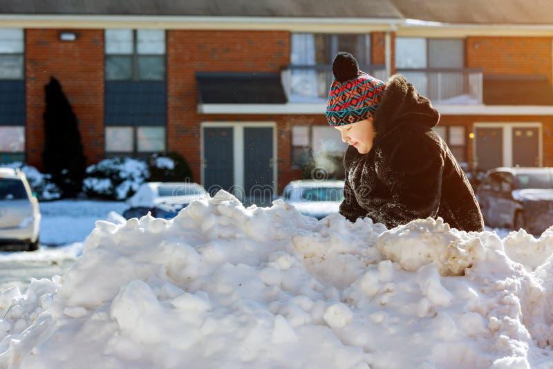 Meisje die sneeuw op de manier van de huisaandrijving scheppen Mooie sneeuwtuin of voorwerf Kind met schop het spelen in openluch stock foto