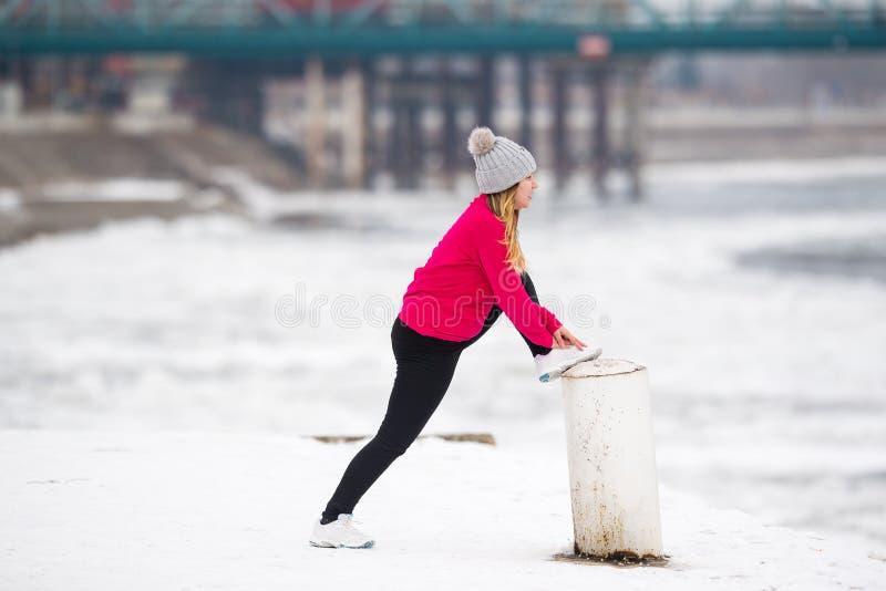 Meisje die sportkleding dragen en uitrekkende oefeningen op sneeuw doen stock afbeeldingen