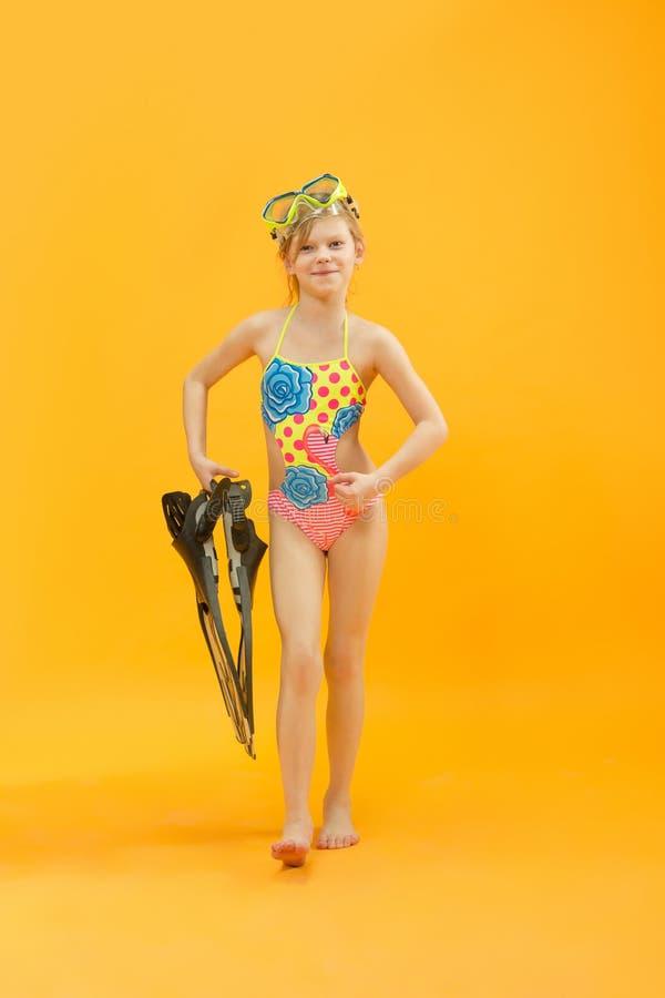 Meisje die swimwear status met snorkelers en vinnen dragen stock foto's