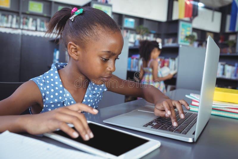 Meisje die tabletcomputer en laptop in bibliotheek met behulp van stock fotografie