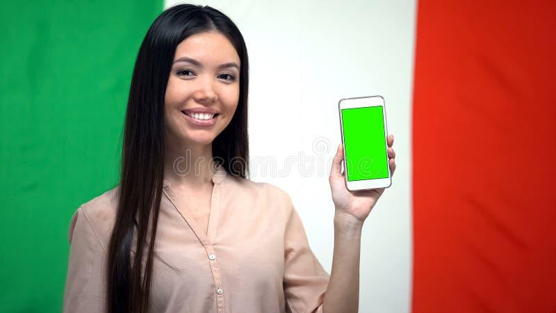 Meisje die telefoon met het groene scherm, Italiaanse vlag op achtergrond, vertaler tonen stock foto's