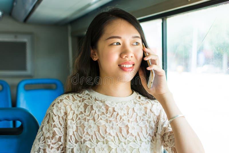 Meisje die telefoon op openbare bus met behulp van stock afbeelding