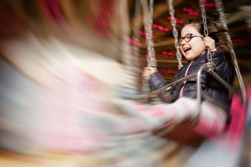 Meisje die terwijl het berijden van een carrousel glimlachen; het opzettelijke effect van het motieonduidelijke beeld stock fotografie