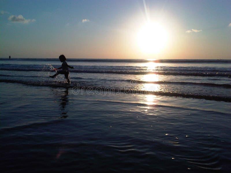 Meisje die terwijl zonsondergang spelen royalty-vrije stock afbeelding