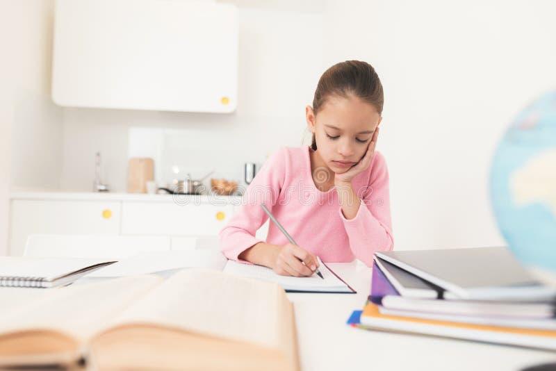 Meisje die thuiswerk in de keuken doen Zij kijkt zorgvuldig in het handboek stock afbeeldingen