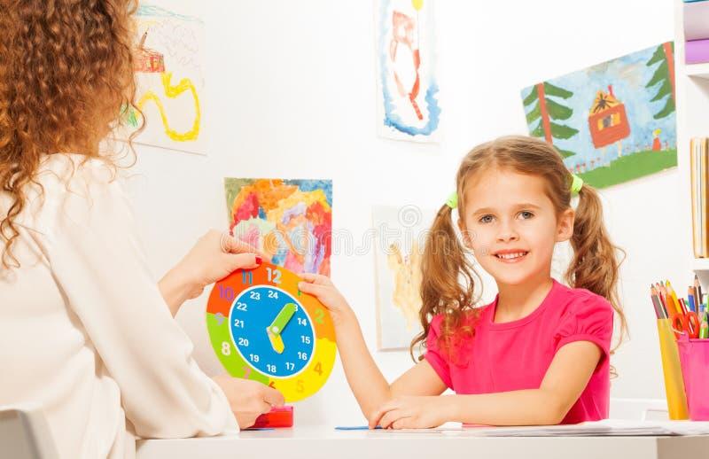 Meisje die tijd met het model van de kartonklok bestuderen stock fotografie