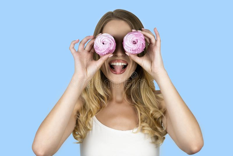 Meisje die twee cupcakes houden dichtbij haar gezicht geïsoleerde blauwe achtergrond stock fotografie