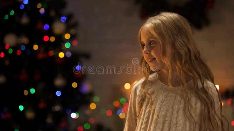 Meisje die uit Kerstman dichtbij gloeiende Kerstboom, vakantieanticiperen kijken stock foto