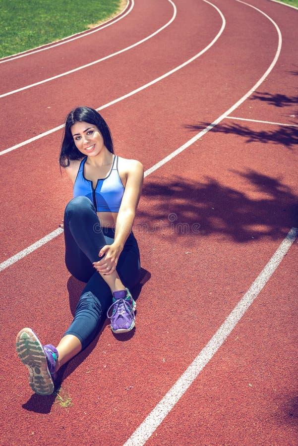 Meisje die uitrekkende oefeningen op spoor doen stock fotografie