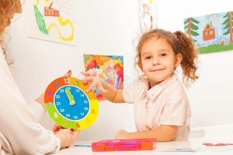 Meisje die uren en notulen bestuderen bij de klok stock fotografie