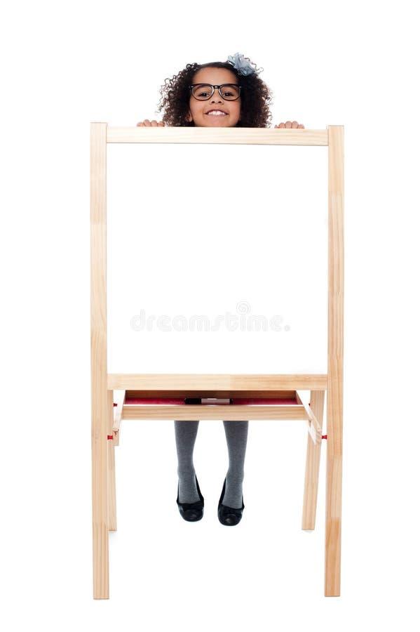 Meisje die van achter witte lege raad piepen stock afbeeldingen