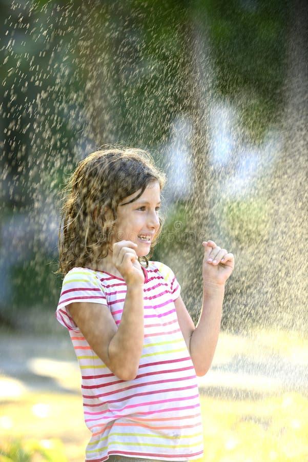 Meisje die van de lichte de zomerregen genieten royalty-vrije stock afbeelding