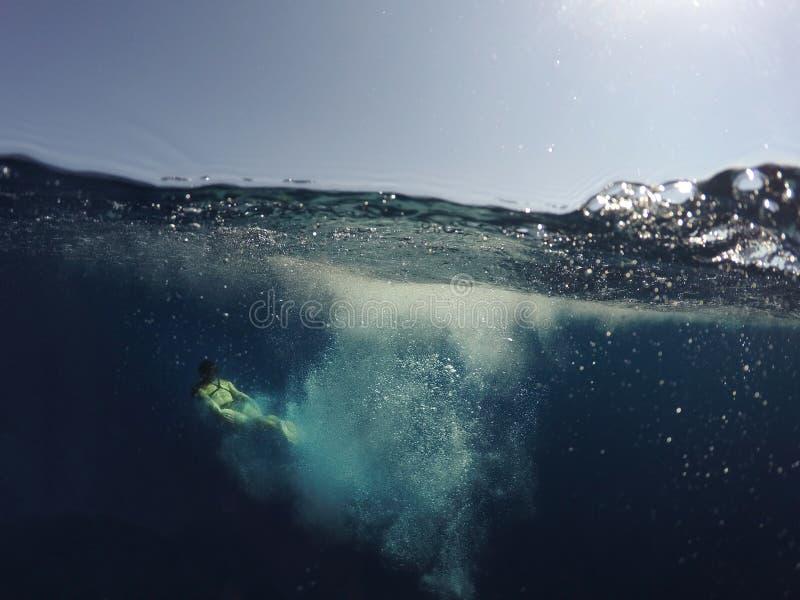 Meisje die van de zeilboot in het duidelijke tropische overzees springen royalty-vrije stock afbeeldingen