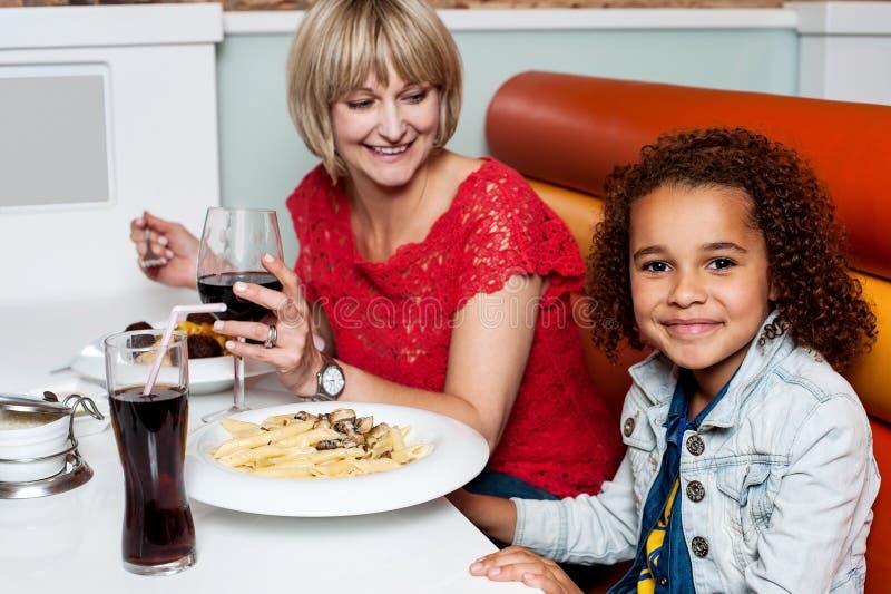 Meisje die van diner met haar mamma genieten stock afbeeldingen