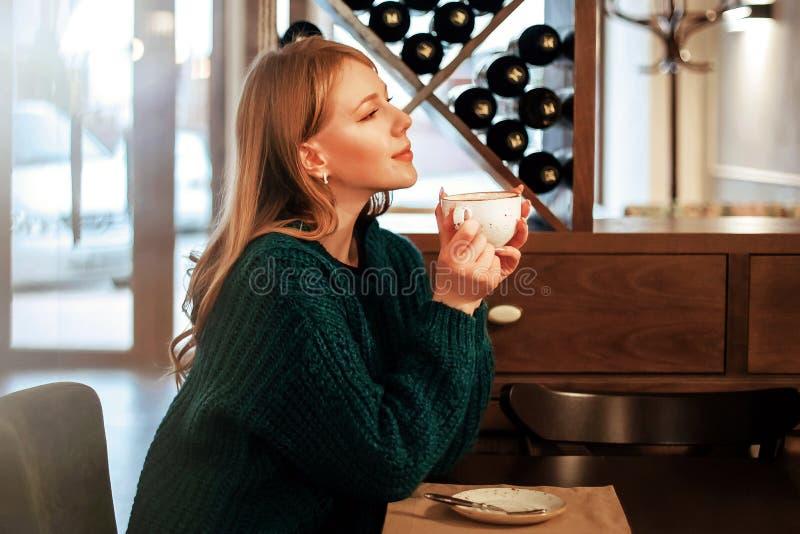 Meisje die van geurige koffie in de koffiewinkel genieten royalty-vrije stock foto's