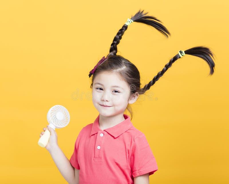 Meisje die van koele wind van elektrische ventilator genieten stock foto