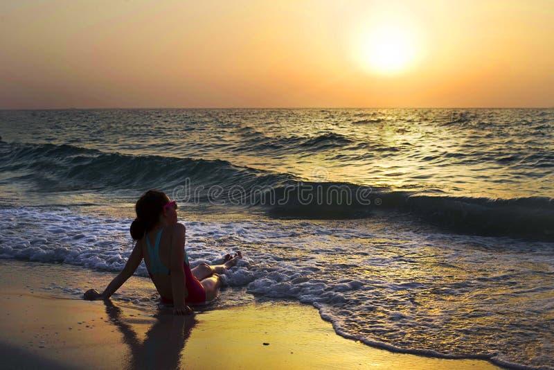 Meisje die van zonsondergang genieten bij de oceaan stock afbeelding