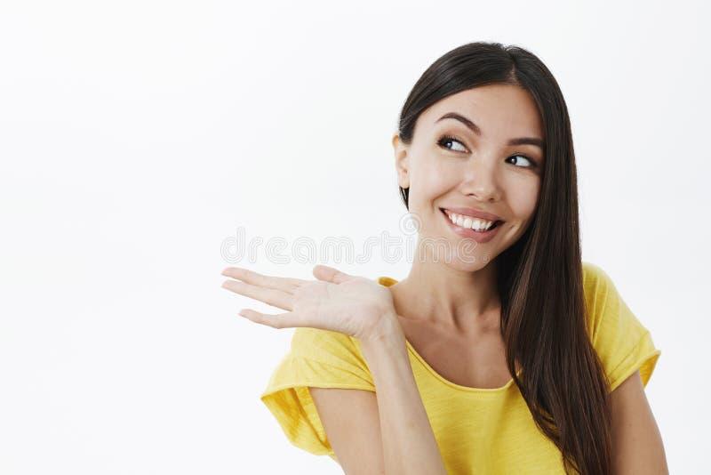 Meisje die veranderd product tonen haar leven Portret van blij tevreden leuk Europees wijfje met donker haar in in geel t royalty-vrije stock foto's