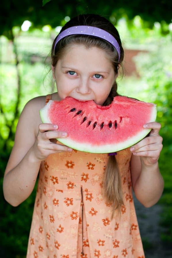 Meisje die verse watermeloen eten stock fotografie