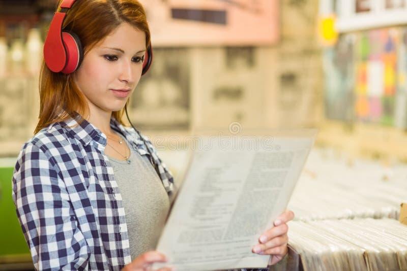 Meisje die vinyl zoeken terwijl het luisteren aan muziek stock afbeelding