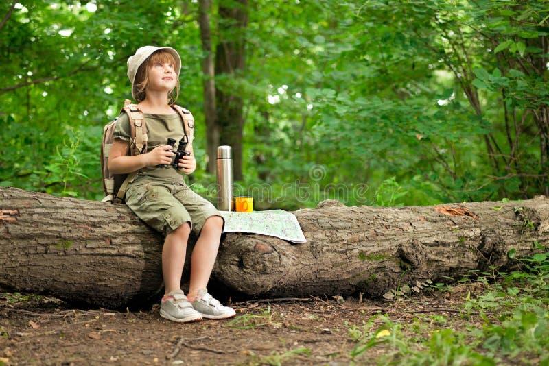 Meisje die vogels door verrekijkers kijken, die in het hout kamperen stock foto