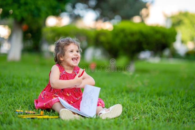 Meisje die voor het kleuren leren of verf trekken op groen gras in aard bij tuin royalty-vrije stock afbeeldingen