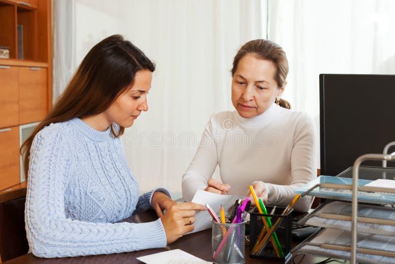 Meisje die vragen van werknemer met laptop beantwoorden stock foto