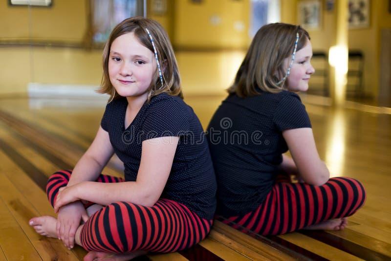 Meisje die in vrijetijdskleding met de benen over elkaar op de vloer van een dansestudio zitten stock afbeeldingen