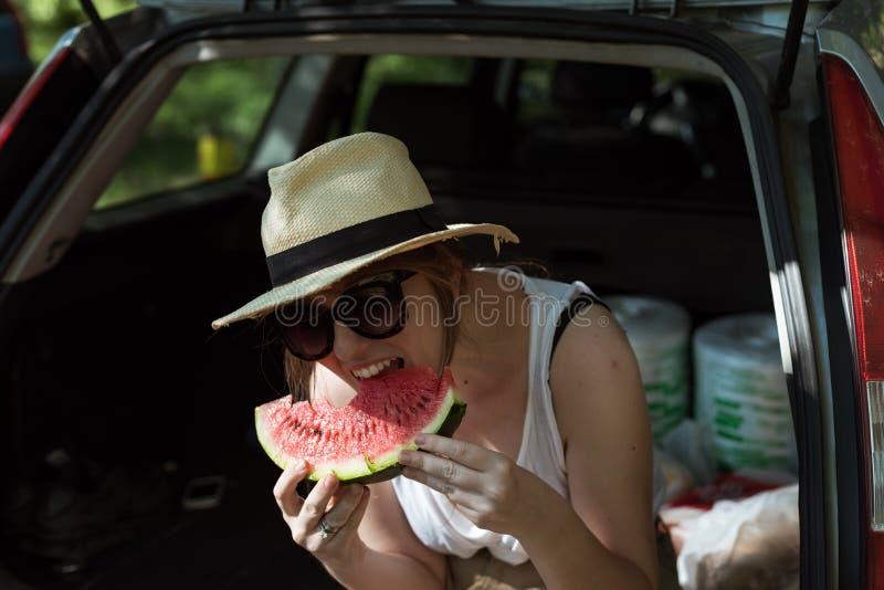 Meisje die watermeloen buiten eten stock fotografie