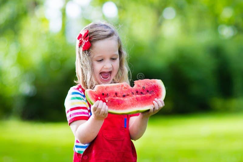 Meisje die watermeloen in de tuin eten royalty-vrije stock afbeeldingen