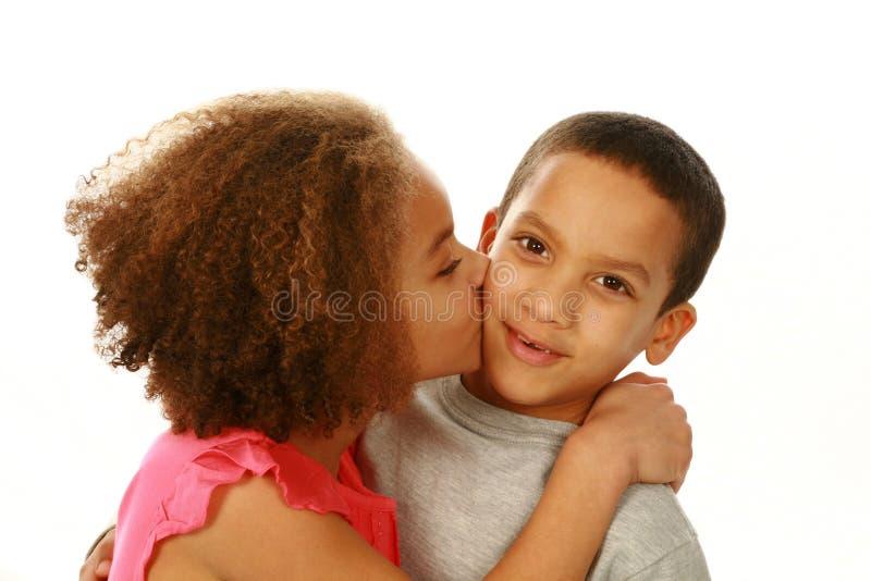 Meisje die weinig jongen op wang kussen stock foto's