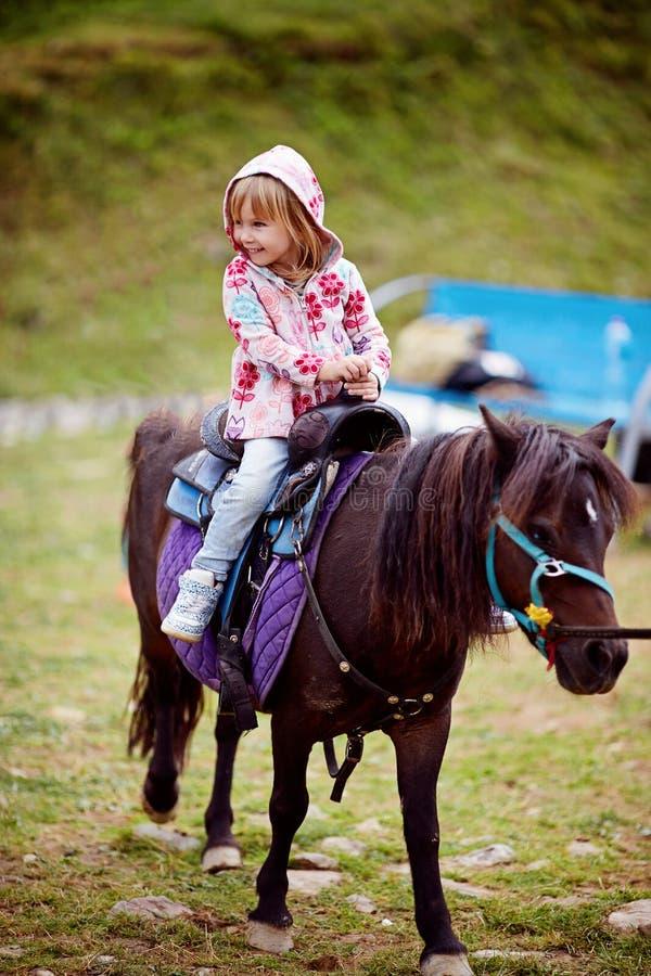 Meisje die weinig poney berijden stock afbeeldingen