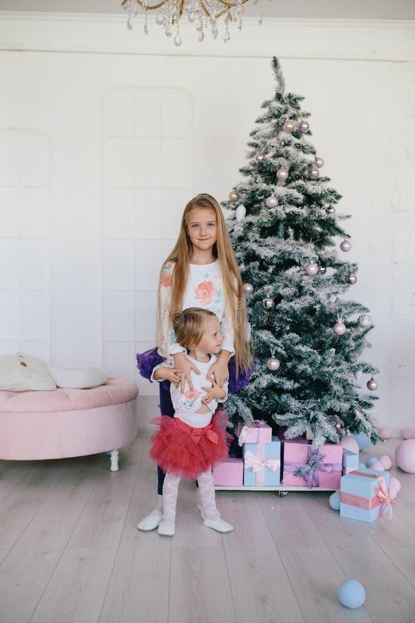 Meisje die weinig zuster koesteren dichtbij een Kerstboom en giftdozen royalty-vrije stock afbeelding