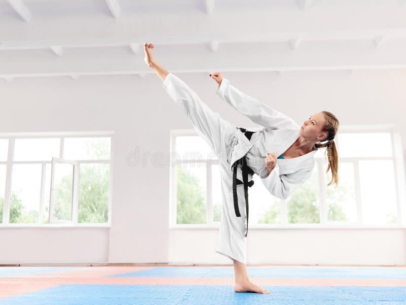 Meisje die in witte kimono dragen die vaardigheid van de vechtsporten de hoge schop uitvoeren royalty-vrije stock afbeeldingen