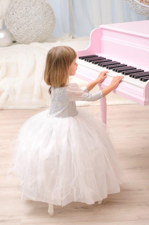 Meisje die in witte toga roze grote piano spelen royalty-vrije stock foto's