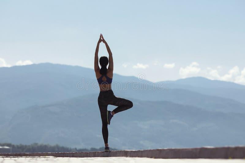 Meisje die yoga in de ochtend, op de waterkant doen door het overzees royalty-vrije stock foto's