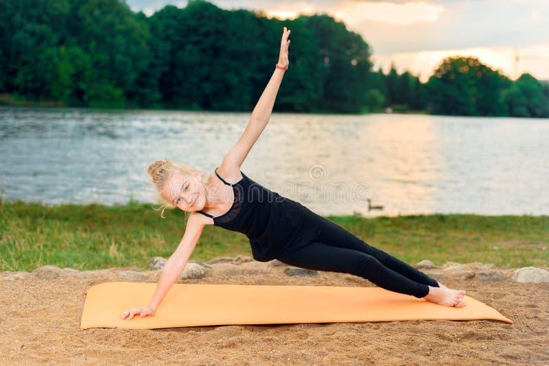Meisje die yoga doen bij zonsondergang door rive royalty-vrije stock foto's