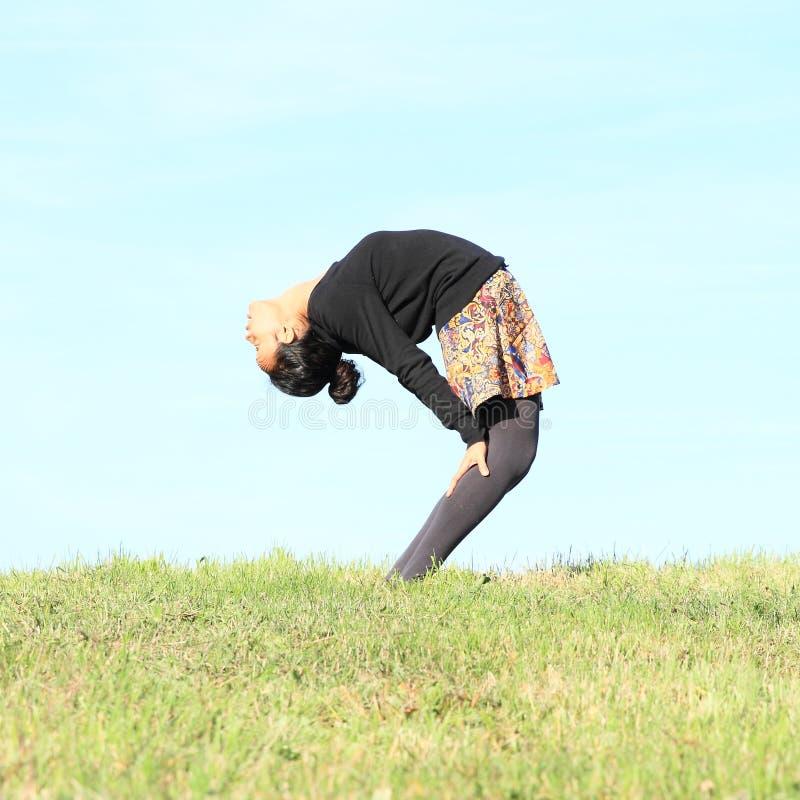 Meisje die yoga op weide uitoefenen royalty-vrije stock foto's