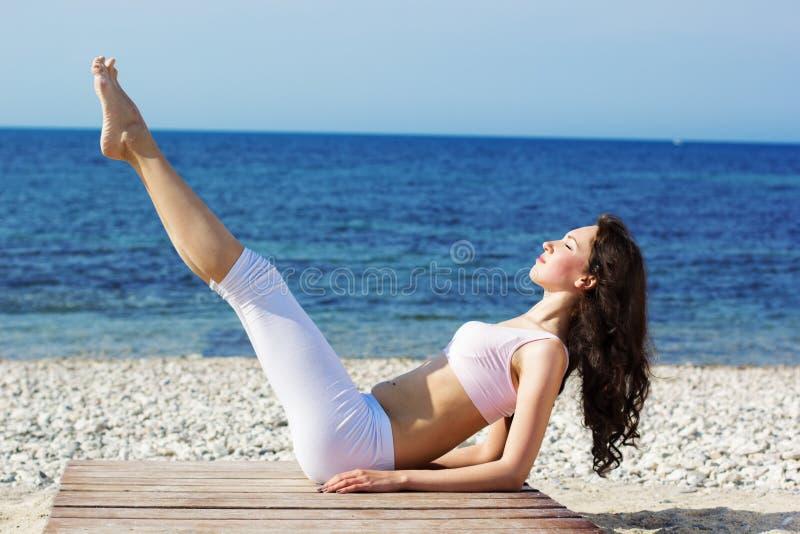 Meisje die yogaoefeningen op de overzeese kust doen stock fotografie