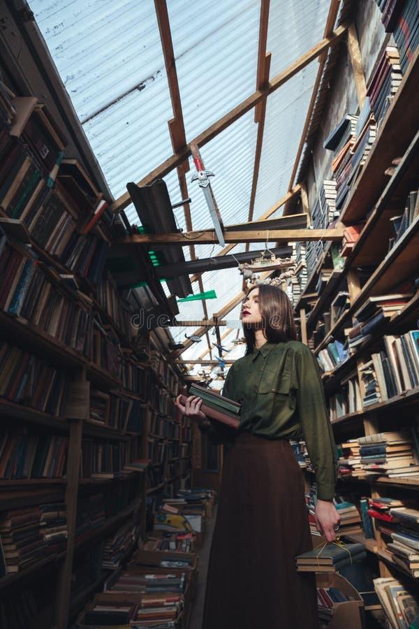 Meisje die zich in bibliotheek met boeken bevinden royalty-vrije stock fotografie