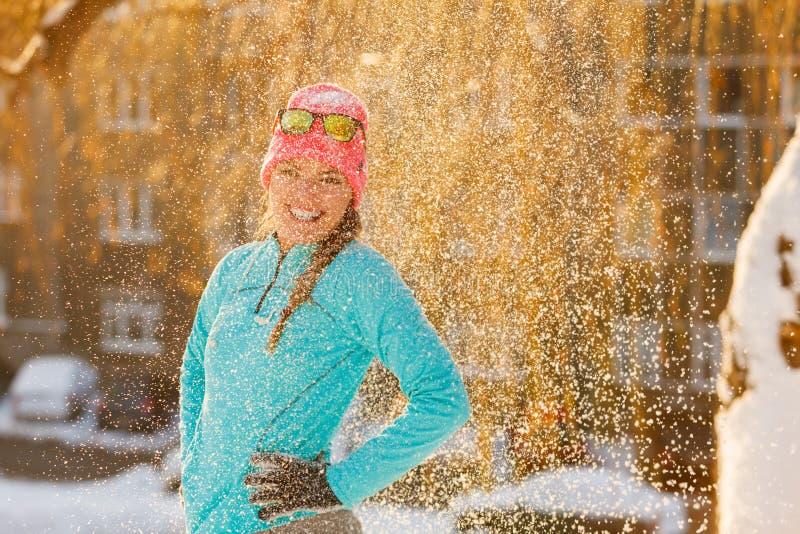 Meisje die zich in dalende sneeuw bevinden stock fotografie