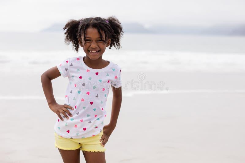 Meisje die zich met hand op heup op het strand bevinden royalty-vrije stock fotografie