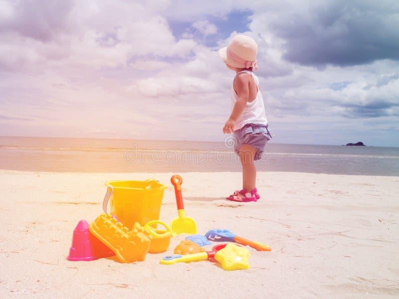 Meisje die zich met speelgoed op tropisch zandstrand bevinden royalty-vrije stock afbeeldingen