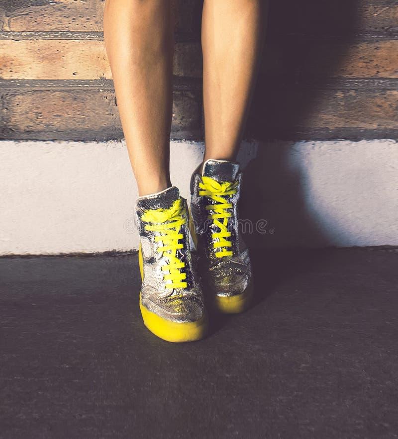 Meisje die zich in modieuze tennisschoenenbakstenen muur bevinden Stedelijke manier stock foto's