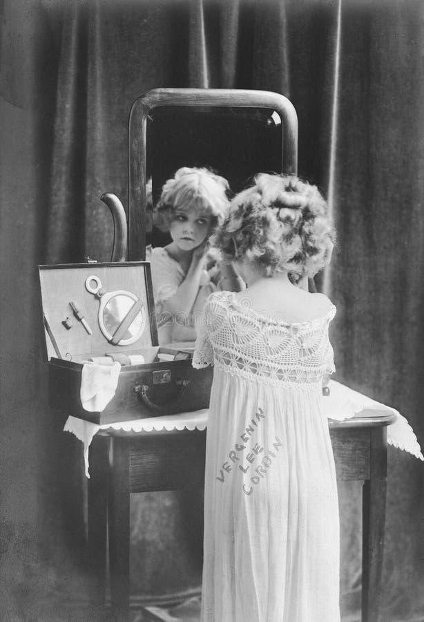 Meisje die zich omhoog voor spiegel kleden (Alle afgeschilderde personen leven niet langer en geen landgoed bestaat Leveranciersg stock afbeeldingen