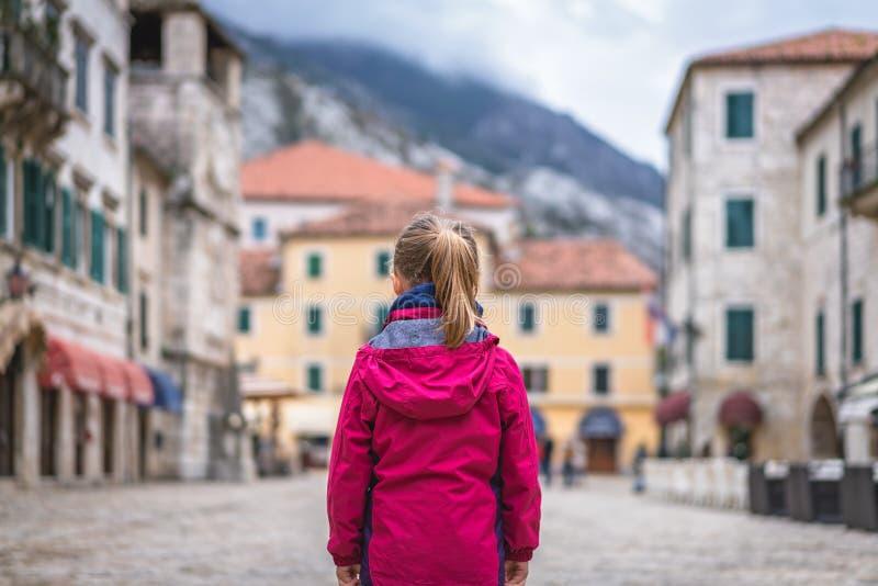 Meisje die zich op het Oude de Stads belangrijkste vierkant van Kotor bevinden stock foto