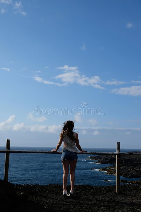 Meisje die zich op vulkanische rotsen bevinden die aan het overzees kijken stock foto