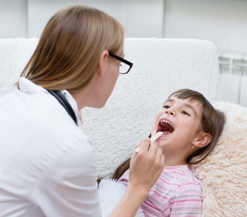 Meisje die zijn die keel hebben door gezondheidswerker wordt onderzocht royalty-vrije stock afbeeldingen